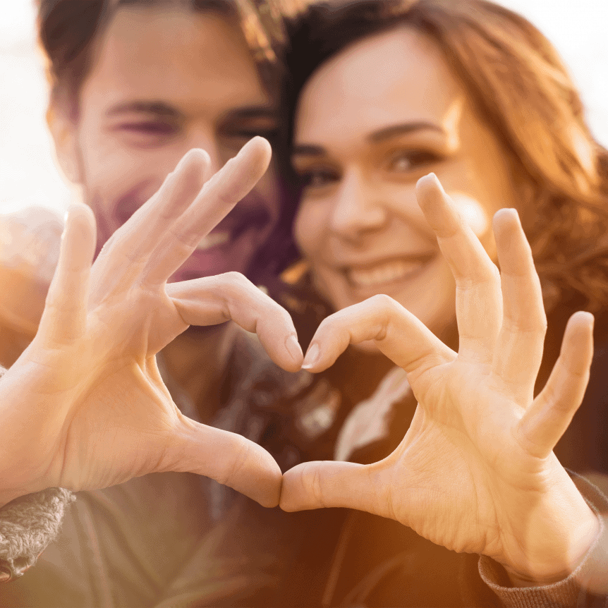 A man and a woman smile with their heads together. They're joining their hands in a heart shape in front of their faces.