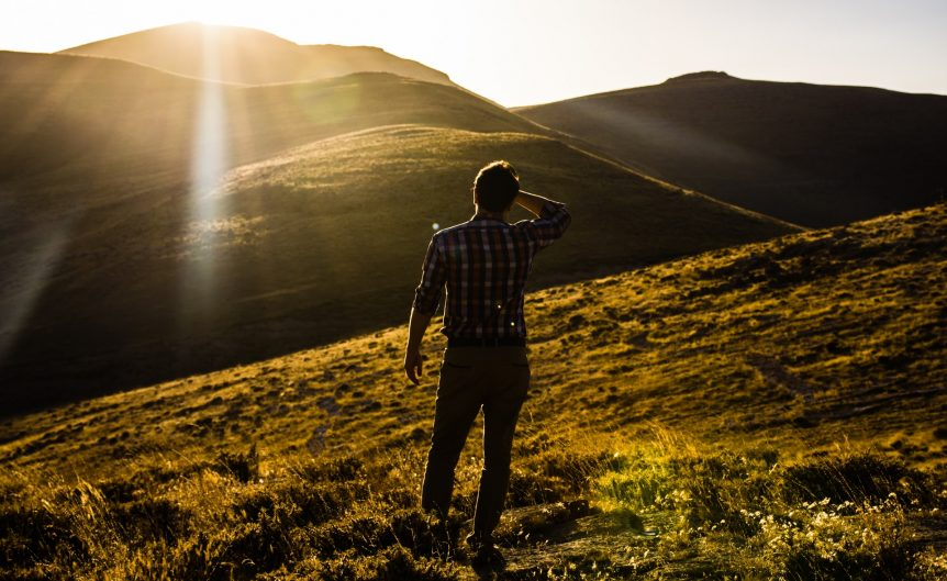 A man on a grassy hill stands with his back to the camera. He is looking ahead with his hand shielding his eyes from the sun.